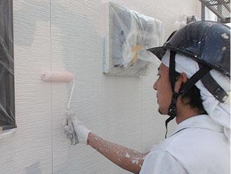 外壁に塗装を施している作業員