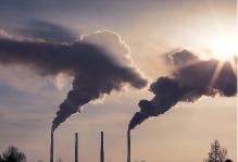 煙突から煙をだす工場の写真
